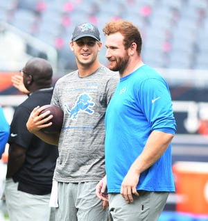 Lions quarterback Jared Goff and center  Frank Ragnow talk on the field during warmups before taking on the Bears.