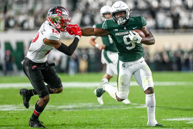 Michigan State's Kenneth Walker III, right, stiff arms Western Kentucky's Kahlef Hailassie on a run during the second quarter on Saturday, Oct. 2, 2021, at Spartan Stadium in East Lansing.