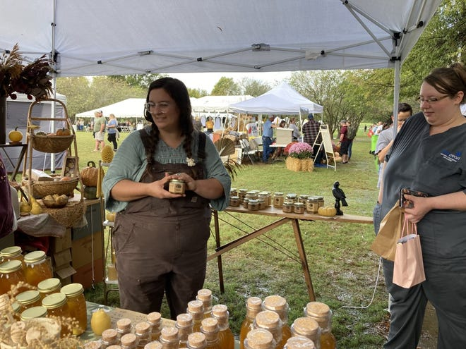 Once Upon a Willow Tree owner Morgan Curtis, left, speaks with a customer about her local honey and beeswax candles at the 2021 Tennessee Honey Festival in Nashville, Tenn. on Oct. 3, 2021.