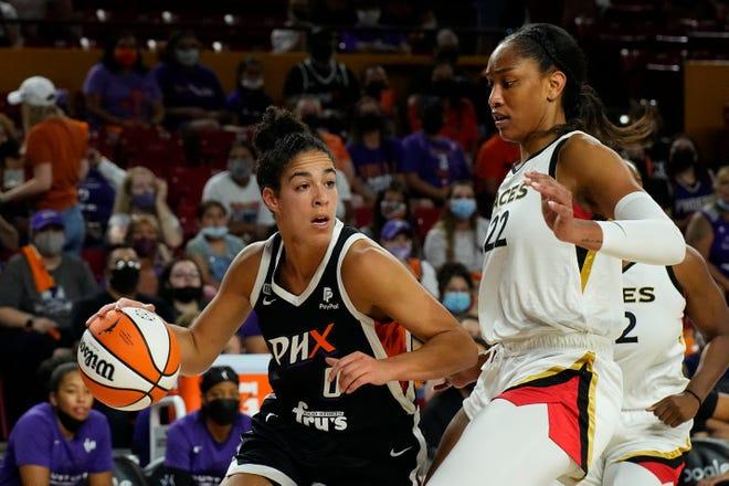 Phoenix Mercury guard Kia Nurse (0) drives on Las Vegas Aces forward A'ja Wilson during the first half of a WNBA basketball game Sunday, Oct. 3, 2021, in Phoenix. (AP Photo/Rick Scuteri)