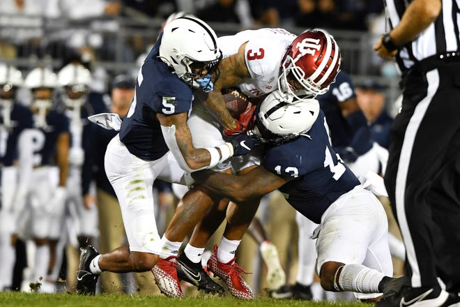 Penn State defenders Tariq Castro-Fields (5) and Ellis Brooks (13) tackle Indiana wide receiver Ty Fryfogle (3) during the second quarter of their NCAA college football game in State College, Pa., on Saturday, Oct. 02, 2021. Penn State defeated Indiana 24-0. (AP Photo/Barry Reeger)