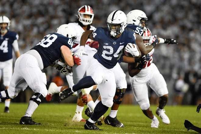 Penn State running back Keyvone Lee (24) breaks away from Indiana defenders on a run in the first half of their NCAA college football ga me in State College, Pa., on Saturday, Oct. 02, 2021. (AP Photo/Barry Reeger)