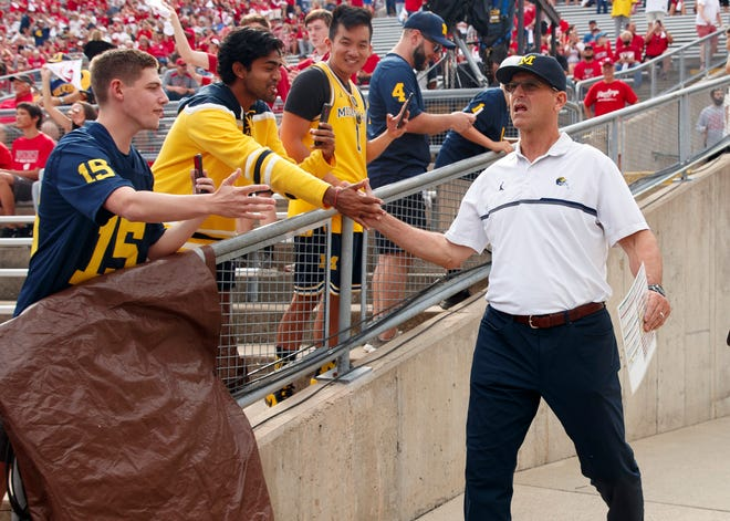 Michigan head coach Jim Harbaugh greets fans prior to the Wolverines' game against the Wisconsin Badgers.