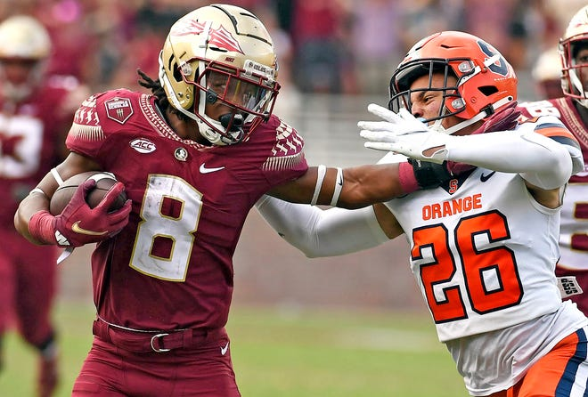 Florida State running back Treshaun Ward (8) tries to stiff-arm his way past Syracuse defensive back Aman Greenwood (26) during the second half.