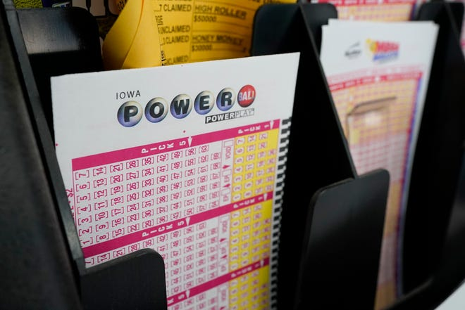 In this Jan. 12, 2021, file photo, blank forms for the Powerball lottery sit in a bin at a local grocery store, in Des Moines, Iowa.