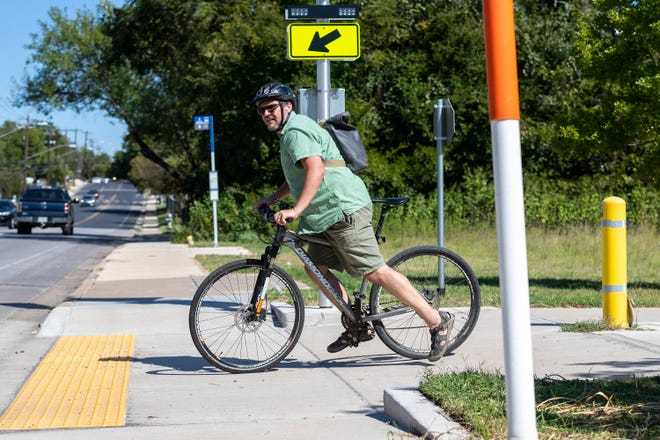 Rob Schuwerk uses a new hike-and-bike trail along Capital Metro's Red Line crossing East 12th Street between Airport Boulevard and Pleasant Valley Road on Monday. The Gannett Foundation has awarded grants to more than a dozen Austin-area organizations, including some that have improved hike-and-bike trails.