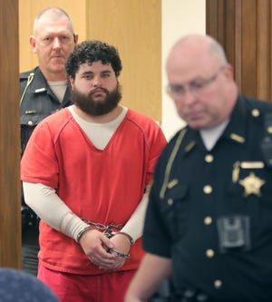 Justin Hornbeck is escorted into Medina County Common Pleas Court on Monday to plead guilty to charges related to the death of Iron Cannon.