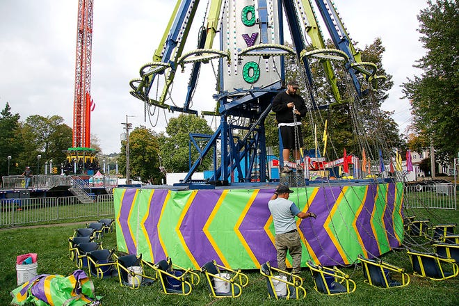 Workers hook up the chairs on the Yoyo ride as setting up for the Loudonville Street Fair was taking place on Monday, Oct. 4, 2021. The Loudonville Street Fair opens on Tuesday, Oct. 5 and runs through Saturday, Oct. 9. TOM E. PUSKAR/TIMES-GAZETTE.COM