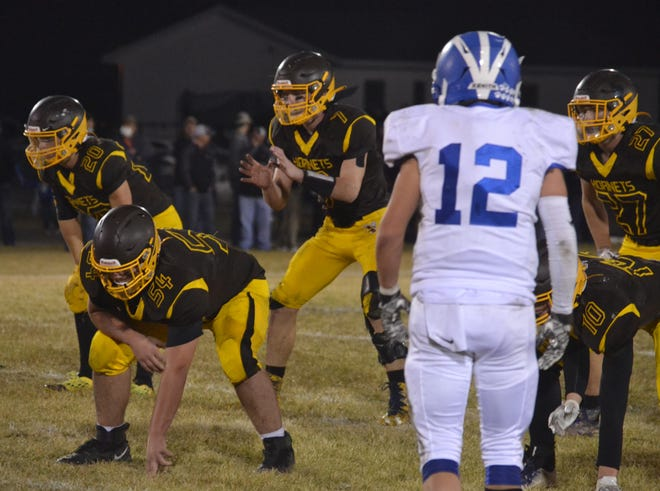 Pellston quarterback Isaiah Crawford, middle, gets ready to take a snap during a playoff game against Inland Lakes in Pellston last season. The 6-0 Hornets will travel to take on fellow unbeaten Inland Lakes, also 6-0, on Friday night at 7 p.m.