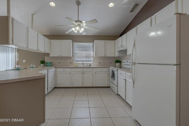 The open and spacious kitchen offers a large eat-in nook, white raised-panel cabinetry, a newer range and refrigerator, and extended counter space.