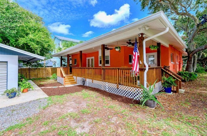 With beautiful porches on the front and back of this New Smyrna Beach home, you can spend endless hours outside, enjoying the mature landscaping and ocean breezes.