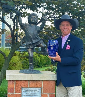 Gaston County native, Lane Evans, holds an award by the United States Professional Tennis Association after being named the Alex Gordon USPTA National Professional of the year.