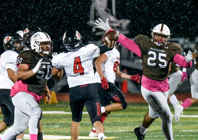 Garden City High School defensive lineman Saul Perez, left, and Xavier Soriano apply pressure to Liberal quarterback Brooks Kappelmann and force an incomplete pass Friday in the rain at Buffalo Stadium. The GCHS defense shut out the Redskins on the night.