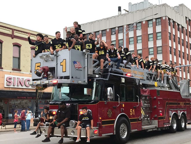 The Galesburg High School Football Team waves and throws candy to those gathered along Main Street during the homecoming parade Friday afternoon. The Streaks lost their homecoming game on Friday night 33-30 in overtime to Rock island. Galesburg is now 2-4 on the season and will play Friday at Moline.