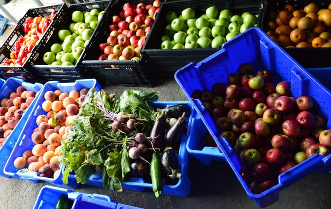 Bins of apples, pears, peaches, peppers and other vegetables and fruits are unloaded at Mother Hubbard's Cupboard as part of the Farm to Family Fund produce that will be available to people in need of food.