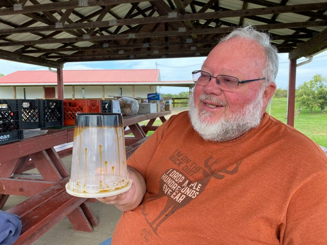 Liberty Lions Club Treasurer Anthony Cochran holds a tub of the molasses that he made the day prior. It's so thick that it won't run down the sides of the container when it's held upside down.