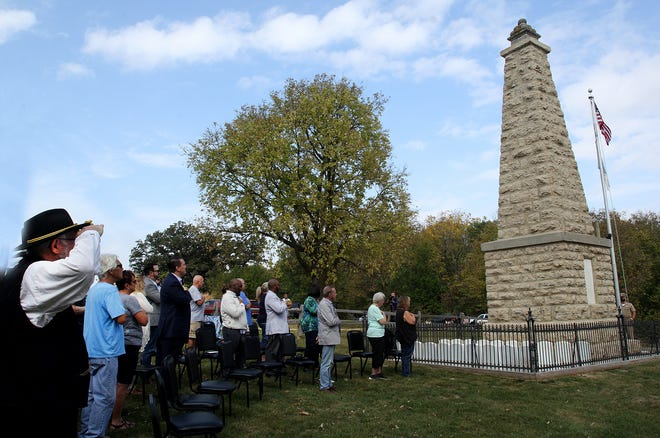 The crowd stands with hands over their hearts as they recite the Pledge of Allegiance during the rededication of the Blackhawk War Monument on Saturday, Oct. 2, 2021, in Kent.