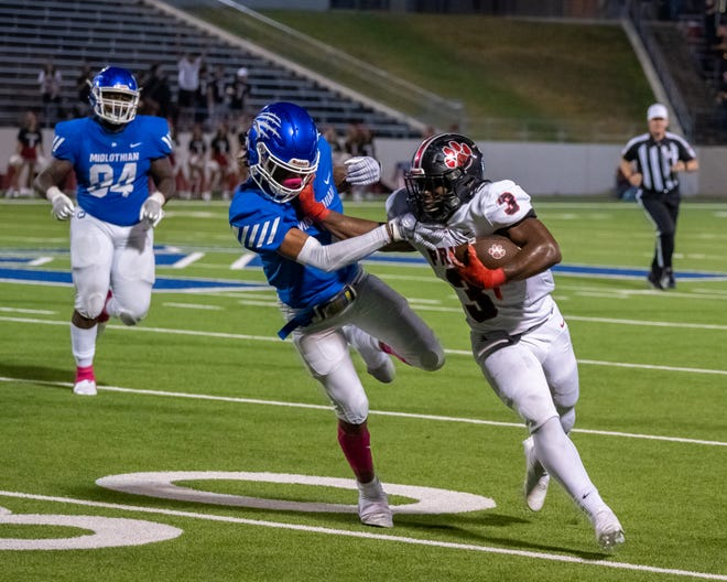 Colleyville Heritage senior running back Isaac Shabay (3) stiff-arms a Midlothian defender during Friday night's District 4-5A (I) game at MISD Multipurpose Stadium.
