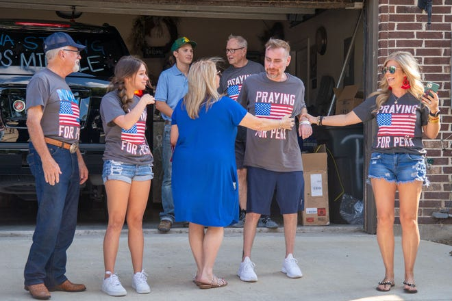 Family and well-wishers gather to welcome Midlothian ISD trustee Richard Peña (second from right) home from the hospital on Thursday after a months-long battle with COVID-19. Peña was stricken with the disease in June, just a month after being elected to the school board.