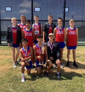 The Heritage boys' cross-country team displays their first-place trophy following Thursday's first-place finish in the Class 1A-4A division of the Ken Gaston Invitational at Lynn Creek Park in Grand Prairie.