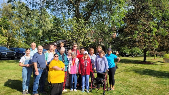 The Schwab family, Elm House residents and two Elm House staff members gather by the newly planted Forest Pansy Redbud tree last week.