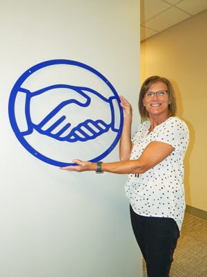 Denneen Smith, Friendship Center executive director, holds up one of the logo fabrications.