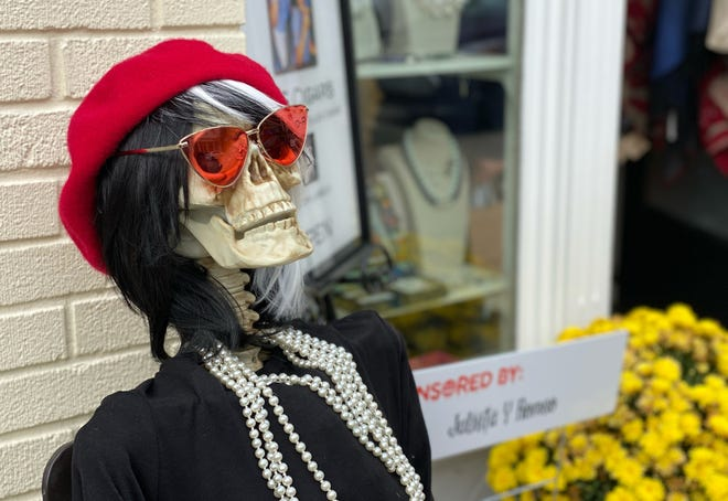 A skeleton can be seen sporting some fashionable jewelry and sunglasses sitting in downtown Harbor Springs.