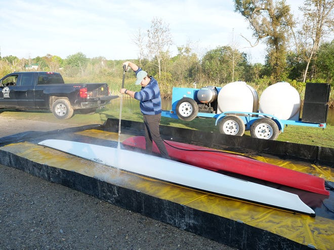 Water resources education coordinator Eli Baker uses the Watershed Council's Mobile Boat Washing Station to clean a kayak prior to Paddle Antrim at Ellsworth River Park. The spray of hot water can dislodge aquatic invasive species and prevent their spread between water bodies.