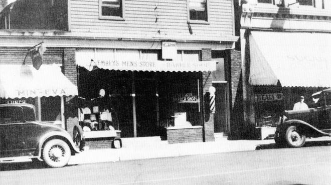 Emrey's Men's Clothing Store on Bridge Street, flanked by Pearl's Barber Shop and Min-Eva Café.