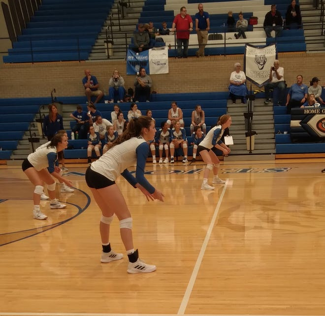 Darby Smith (middle) and her St. John Lady Tigers teammates get ready to field a serve against the Russell Lady Broncos in last week's Thursday volleyball game in St. John.