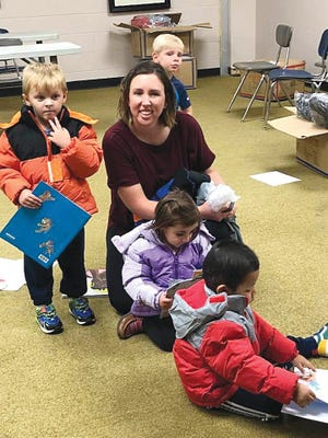 Heather Lynch, a preschool Bridges to Learning teacher, helps youngsters find and fit into new coats provided by the Pratt Elks Lodge, and get into new books from Pratt Public Library, last week in Pratt.