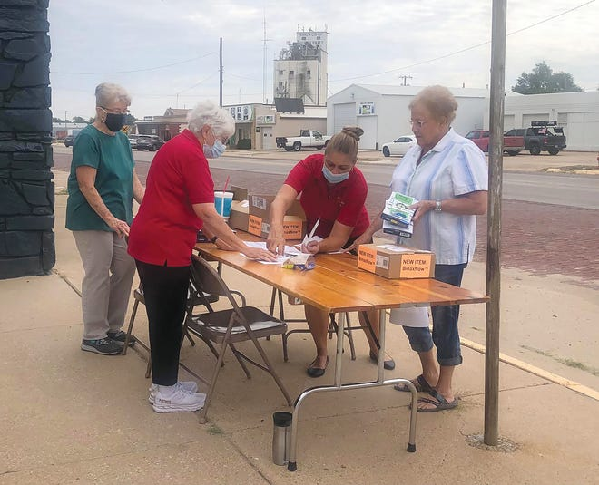 Pratt Pilot Club members Karen Detwiler and Jan Jorns (behind the table) and Tammy Acker Killough (red shirt in front) helped distribute and conduct free COVID-19 tests last week in Pratt.