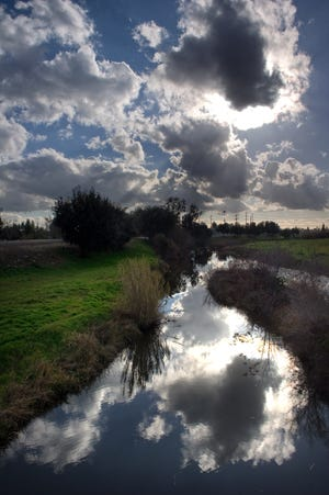 Approaching clouds are reflected in the waters of the Calaveras River near Pershing Avenue in Stockton.