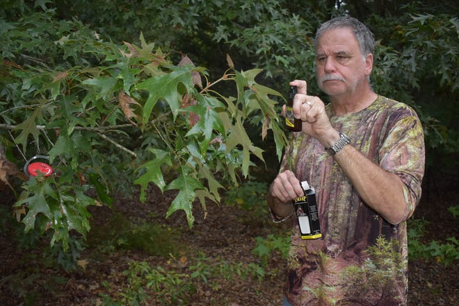 Jeff Rice sprays an overhanging limb with scent from TRHP Outdoors to create a mock scrape.
