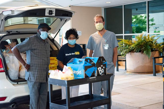 (From left) Pastor Billy Houze, Rev. Elaine Ollemi and a healthcare professional at Atrium Health-Cleveland load up Bojangles biscuits to distribute to essential workers.