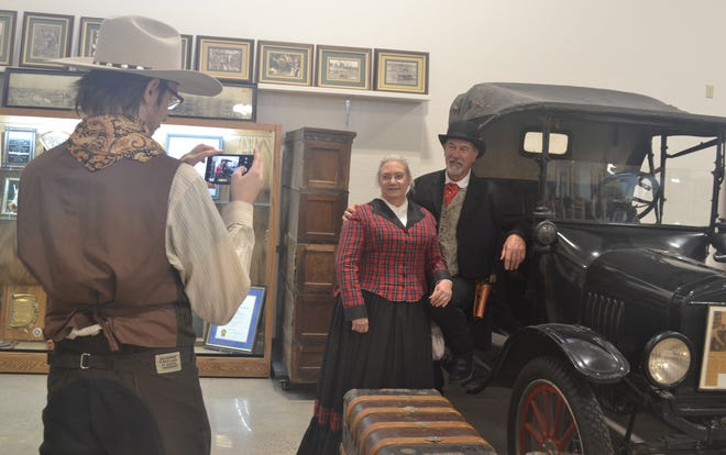 Visitors take pictures with exhibits in the Milburn Center Saturday.
