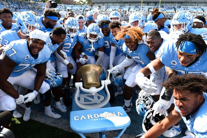 UNC football players celebrate after beating Duke, 38-7, and retaining the rivalry's Victory Bell at Kenan Memorial Stadium on Oct 2, 2021, in Chapel Hill.