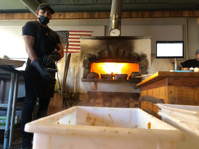 """Each year, Nigel Mendoza, a cook at Rail Trail Flatbread Co. in Hudson, helps Medusa Brewing Co. roast freshly harvested pumpkins for the brewery's pumpkin stout, """"Witchfinder General."""""""
