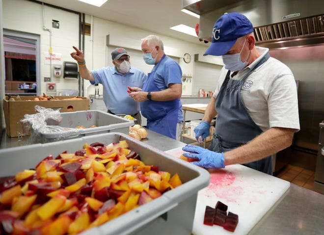 Skip Gardiner, left, Mike Congrove, center, and Bob Donnelly prepare meals for the Loaves and Fishes meal program on Friday, October 1, 2021,213 E. Wisconsin Ave. in Appleton, Wis.