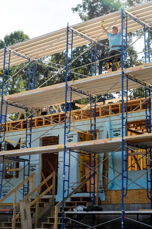 Jan Cosman, a member of the Women Build team at Habitat for Humanity, stands on scaffolding while working on a home in West Asheville September 30, 2021.