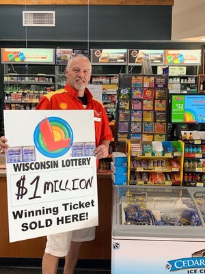 Don Web, district manager of Cougar Shell, holds a sign proclaiming that a $1 million dollar lottery ticket was sold there in September. The prize was won a Coleman man.