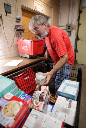Salvation Army volunteer Vince Coonce, of Clark Mills, Wis., picks up donated food items for weighing at the Manitowoc Salvation Army food bank, Monday, October 4, 2021, in Manitowoc, Wis.
