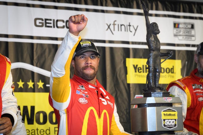 Bubba Wallace celebrates next to the trophy after winning a NASCAR Cup series auto race Monday, Oct. 4, 2021, in Talladega, Ala. The race was stopped mid race due to rain. (AP Photo/John Amis)