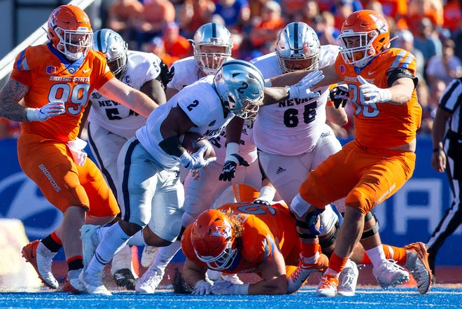 Wolf Pack running back Devonte Lee (2) looks to get around the Boise State defense on Saturday at Albertsons Stadium.