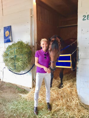 Donna Brothers poses for a photo with American Pharoah.