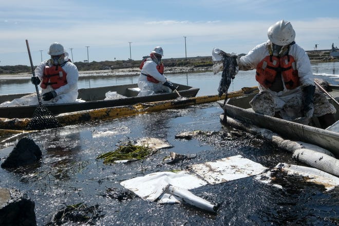 Cleanup contractors deploy skimmers and floating barriers known as booms to try to stop further oil crude incursion into the Wetlands Talbert Marsh in Huntington Beach, Calif., Sunday, Oct. 3, 2021.