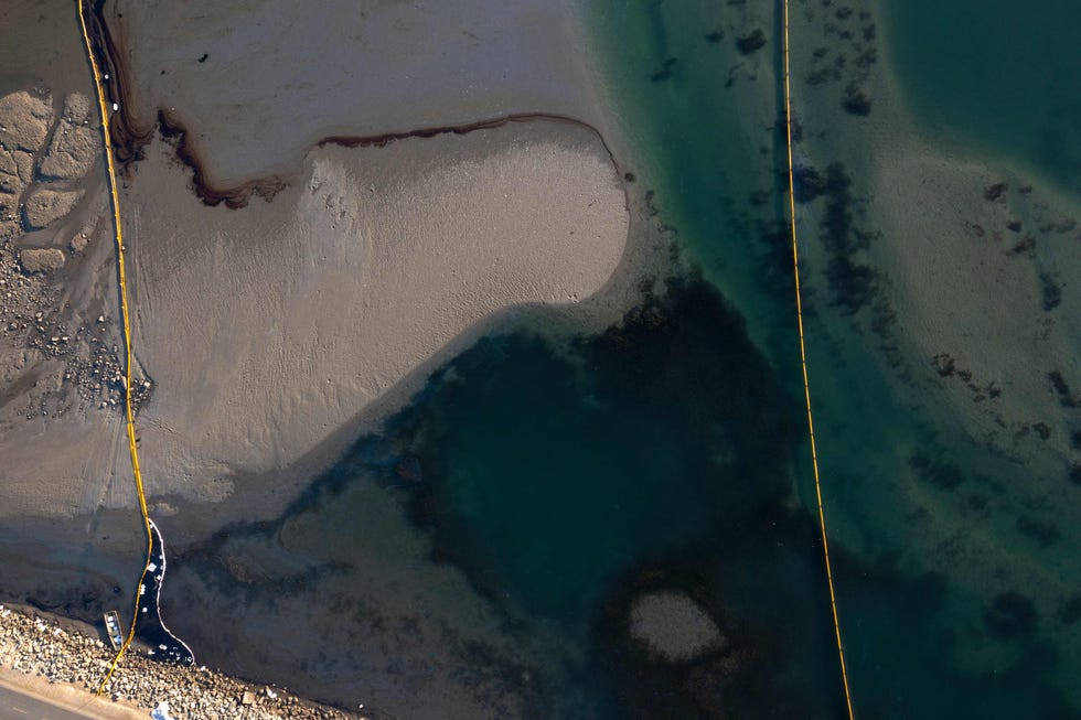 This aerial picture taken on October 3, 2021 shows oil and an oil containment booms in the water of the Talbert Marshlands area from an offshore oil rig as it reaches the shore and sensitive wildlife habitats in Newport Beach, California.