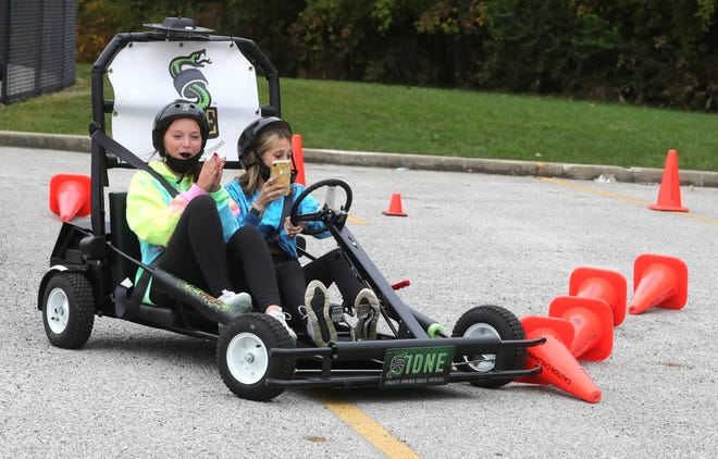 Nordonia High School freshman Olivia Wells, left, and Hailey Wright participate in a distracted driving exercise during Safe Decisions Week. There were a series of outdoor activities at the high school on Tuesday and Wednesday. This photo was taken Tuesday.