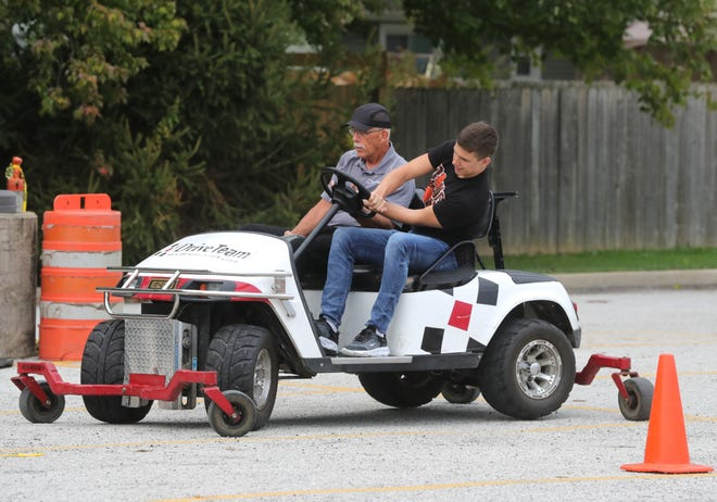 Nordonia High School senior Perry Dangerfield tries to maneuver the skid golf cart with Drive Team instructor Greg Lewicki during Safe Decisions Week.