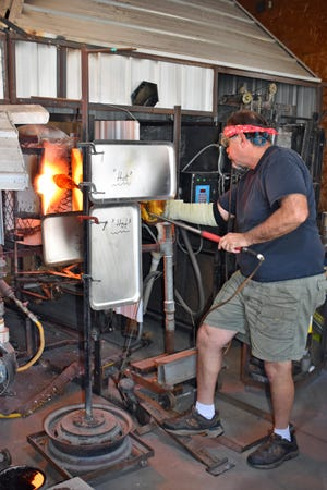 Glassblower Art Ciccotti removes a vase from the furnace at his workshop southwest of Ames Monday. Ciccotti is one of the 11 artists featured in Saturday's Ames Artists' Studio Tour.